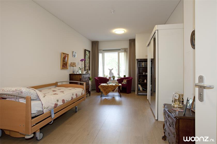 Een slaapkamer van ruim 25 m2, voozien van gordijnen en een bed.